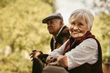 Smiling old woman at park with her husband
