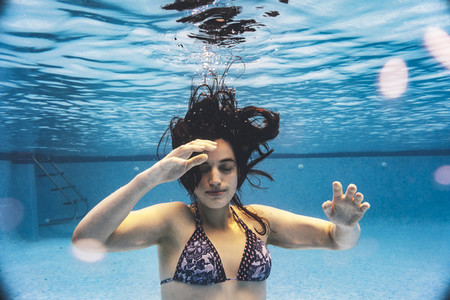 Creative underwater shot  portrait of a young woman enjoying at the pool in summertime
