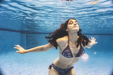 Young woman swimming at surface enjoying at the pool in summertime