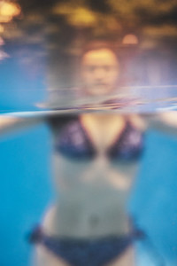 Creative blurry underwater shot  of a young woman enjoying at the pool in summertime