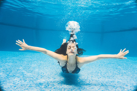Underwater front view of a woman swimming with open arms in a pool at summer time