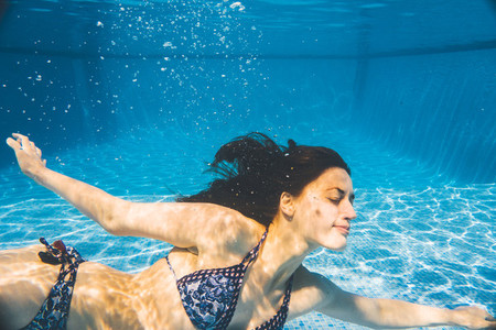 Underwater side view of a woman swimming in a pool summer time