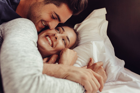Loving couple lying together on bed