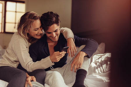 Relaxed couple looking at mobile phone
