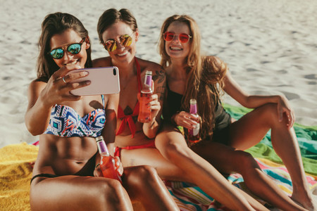 Women sitting at the beach taking a selfie