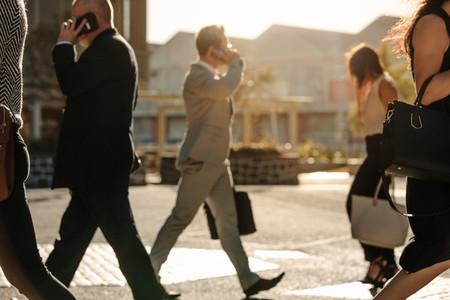 Business people busy using mobile phone while walking on street