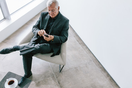 Mature businessman using with phone in office lobby