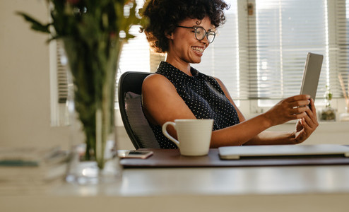 Happy woman using digital tablet in office