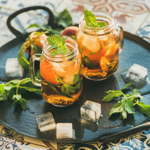 Summer refreshing cold peach ice tea with mint square crop