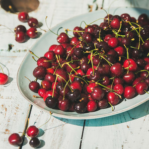 Fresh ripe sweet cherries in plate on rustic garden table