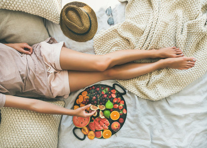 Young girl taking fruit from tray full of fresh fruits