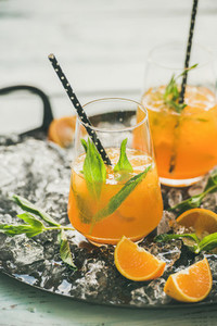 Refreshing cold alcoholic summer cocktail with orange peppermint and ice