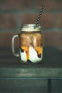 Iced caramel macciato coffee with milk in jar side view