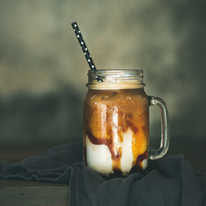 Iced caramel macciato with milk in glass jar square crop