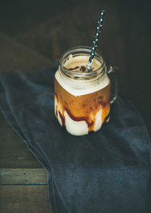 Iced caramel macciato coffee with milk in glass jar