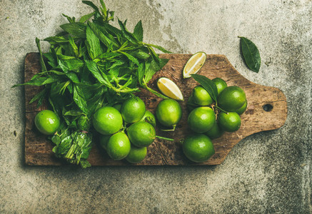Flatlay of fresh limes and mint on wooden board