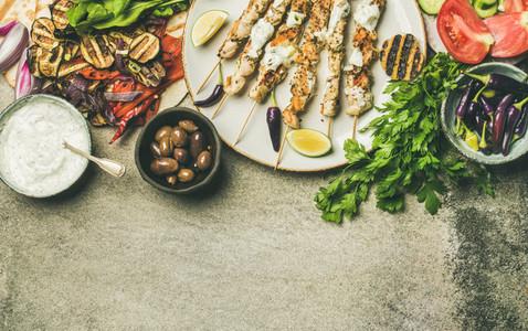 Flatlay of grilled chicken skewers  flatbread  parsley  vegetables  olives