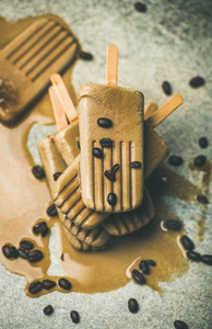Melting coffee latte popsicles with roasted coffee beans top view