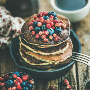 Breakfast with pancakes with forest berries and honey square crop