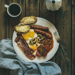 Traditional English breakfast with fried eggs sausages mushrooms bacon coffee