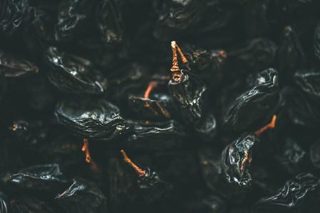 Flat lay of black dried raisins top view close up