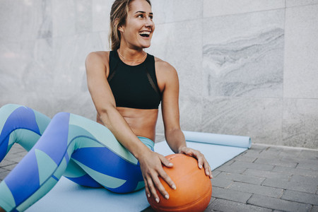 Happy fitness women doing sit ups holding a basketball
