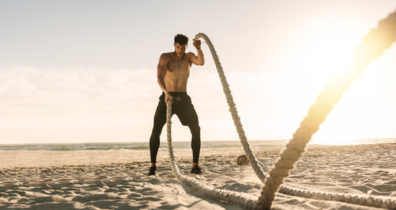 Man doing workout using battling ropes at the beach