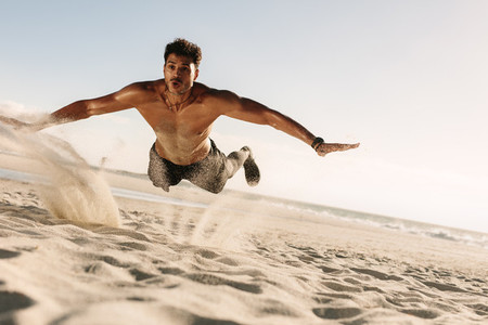 Man doing fitness exercise in beach sand