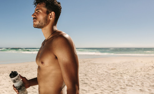 Man standing at the beach drinking water after workout