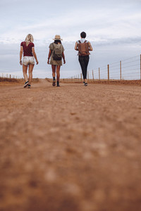 Female friends walking on country road after their car breakdown
