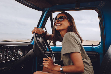 Woman on road trip driving a car and smiling