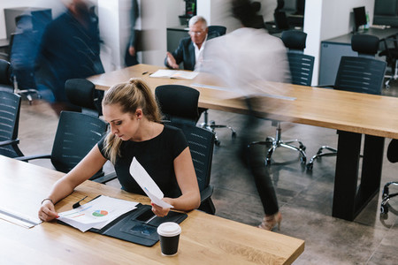 Businesswoman reviewing statistical reports in office