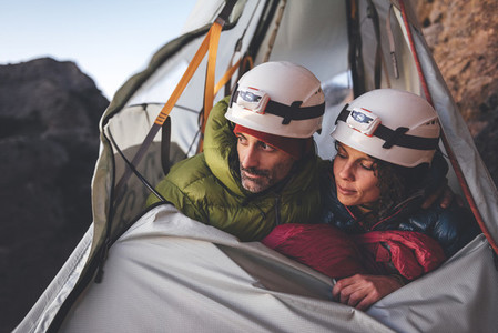 Couple of climbers looking to horizon ready to sleep in a portaledge hanging on the wall in Los Mallos de Riglos  Spain