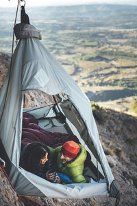 Couple of climbers sharing a morning coffee into a portaledge hanging on the wall in Los Mallos de Riglos  Spain