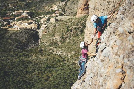 Young couple of climbers giving high five to celebrate a rockclimbing route in Los Mallos de Riglos Spain