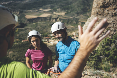 Young couple of climbers attending to rockclimbing guide instructions in a  route in Los Mallos de Riglos Spain