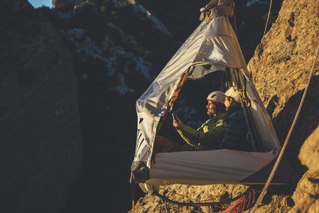 Couple of climbers taking a photo with a digital tablet at sunset in a portaledge hanging on the wall in Los Mallos de Riglos Spain
