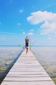 Hot girl doing yoga on pier