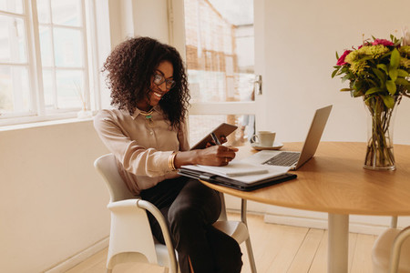 Woman entrepreneur working from home on laptop