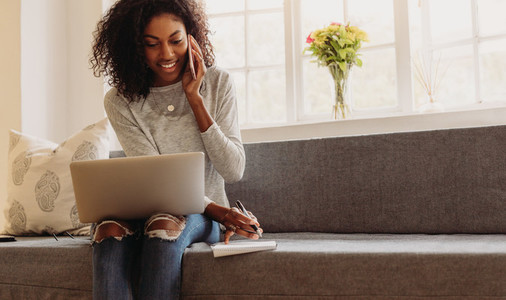 Woman entrepreneur managing business from home with mobile phone
