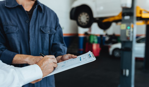 Auto mechanic taking sign on document from customer