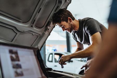 Young mechanic fixing a car