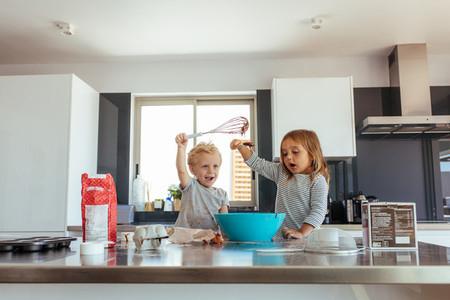 Kids having fun while making cake batter