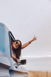 Beautiful woman enjoying traveling by car