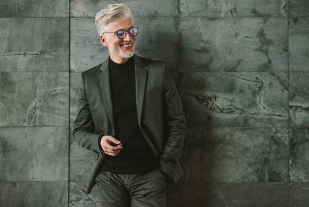 Smiling senior businessman standing on grey wall