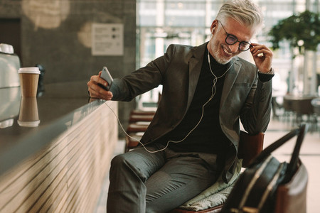 Mature businessman at cafe listening music from cellphone