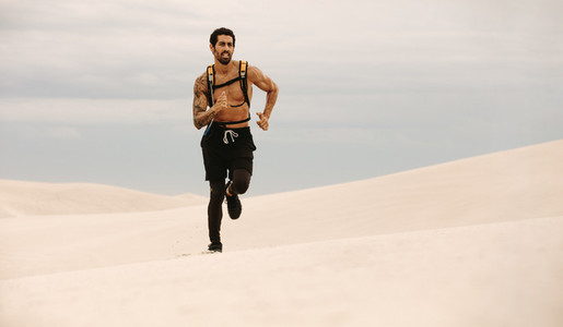 Healthy young man running over sand dunes