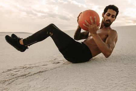 Athlete doing medicine ball workout in desert