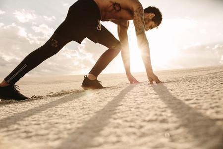 Man about to start a run in desert