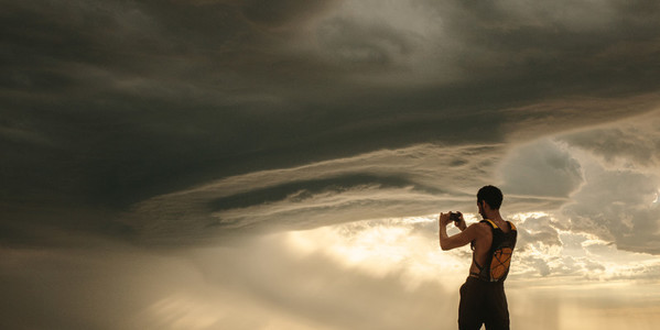 Athlete taking pictures of dramatic sky